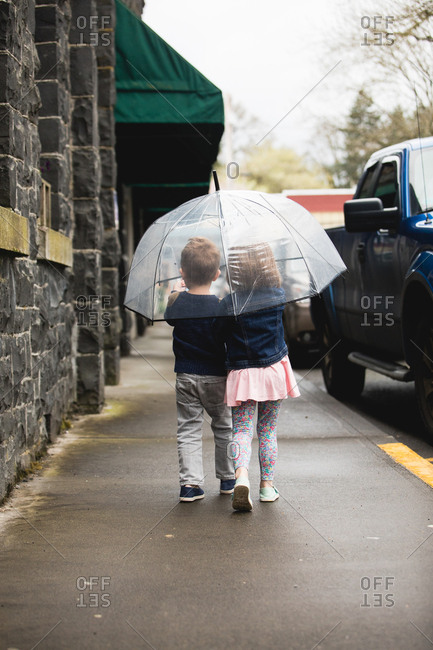 Small children share an umbrella on sidewalk
