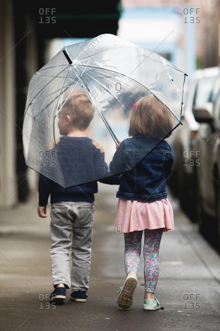 Preschool boy and girl share umbrella on sidewalk