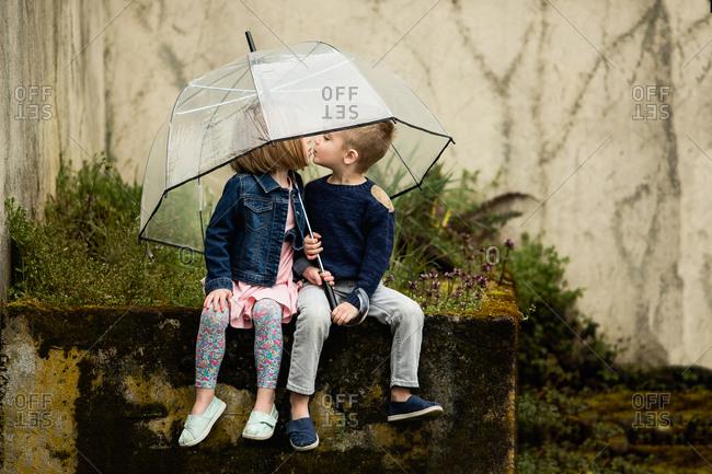 Girl and boy kiss under umbrella