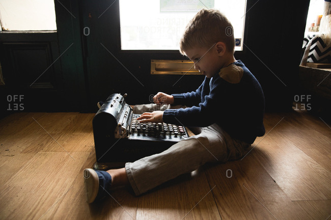 Young boy playing with antique cash register