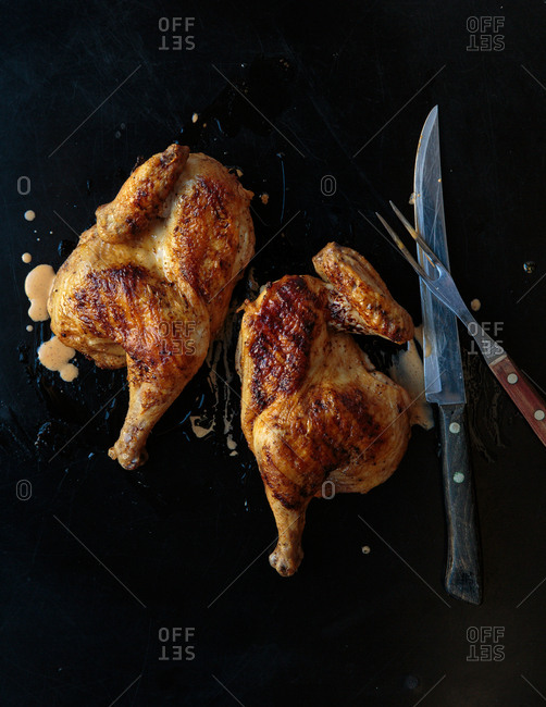 Roasted chicken cut in half with a large knife and fork on a slate