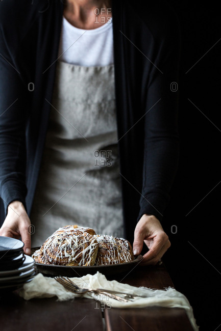 Woman serving plate of cinnamon buns