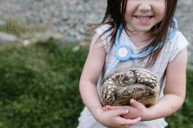 Girl holding turtle wearing toy stethoscope