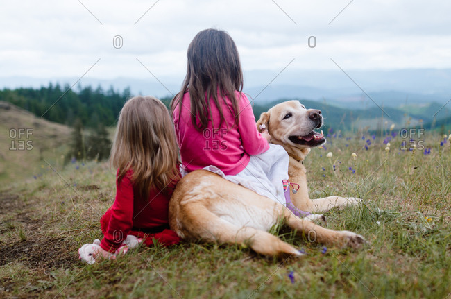 Girls and dog on hill with scenic view