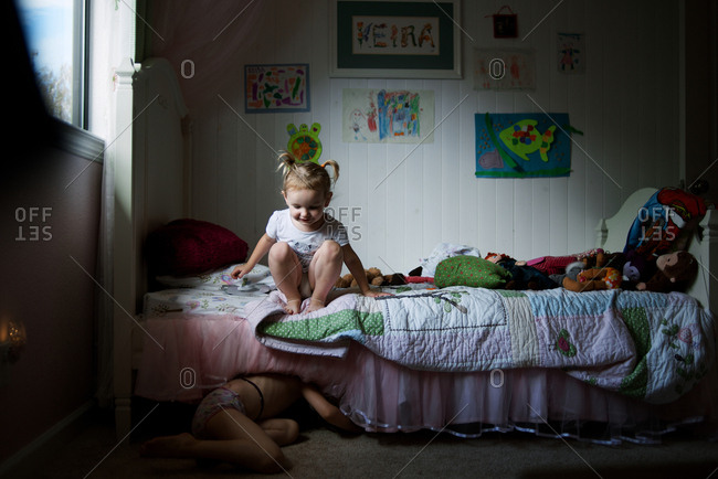 Girl watching sister crawl under bed