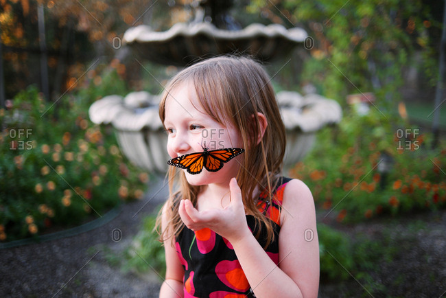 Monarch butterfly lands on girl's face