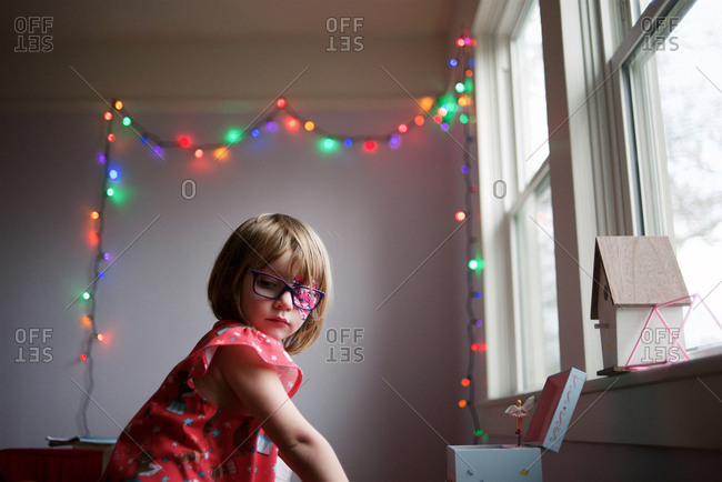 Girl with eye patch under string of lights