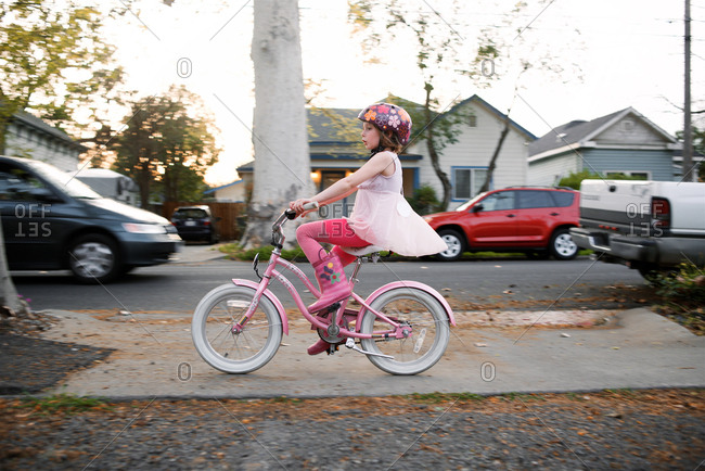 Girl riding her bike down sidewalk