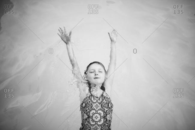 Girl lying on back in swimming pool