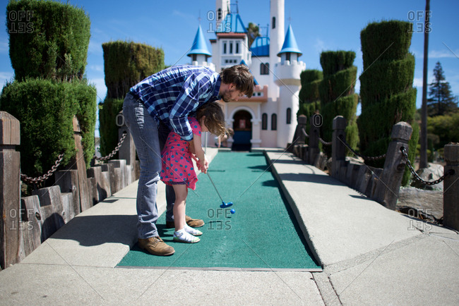 Father and daughter play miniature golf