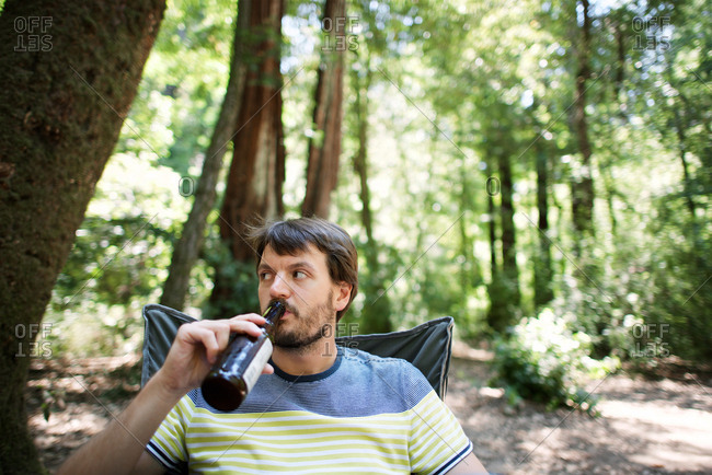 Man drinking beer sitting in woods