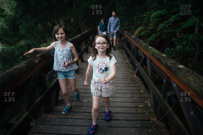 Family hike across rural footbridge, Australia