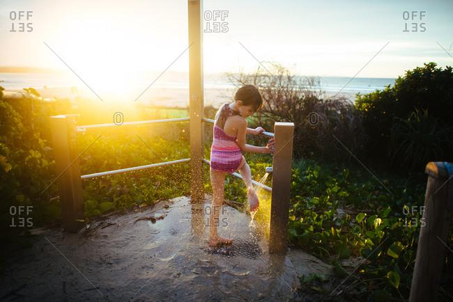 Girl in beach shower washing feet
