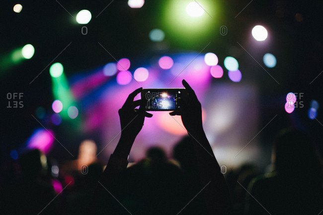 Person taking picture with Smartphone at concert