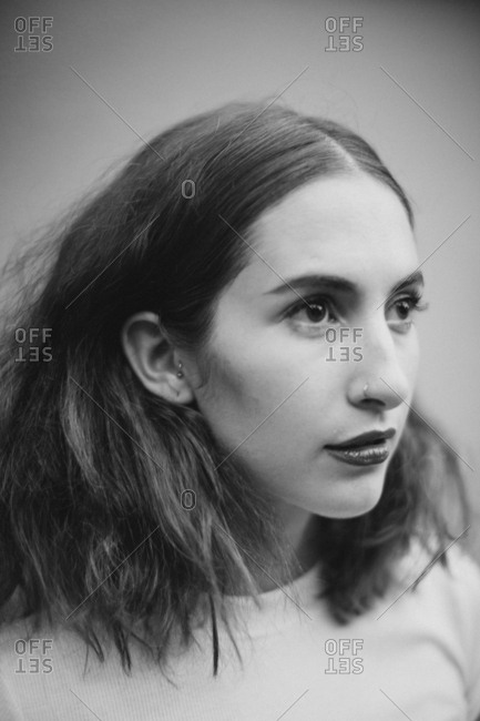 Black and white art portrait of a beautiful young woman with pierced nose