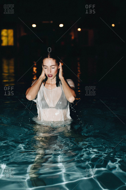 Beautiful young woman going swimming in a pool at night in her clothes