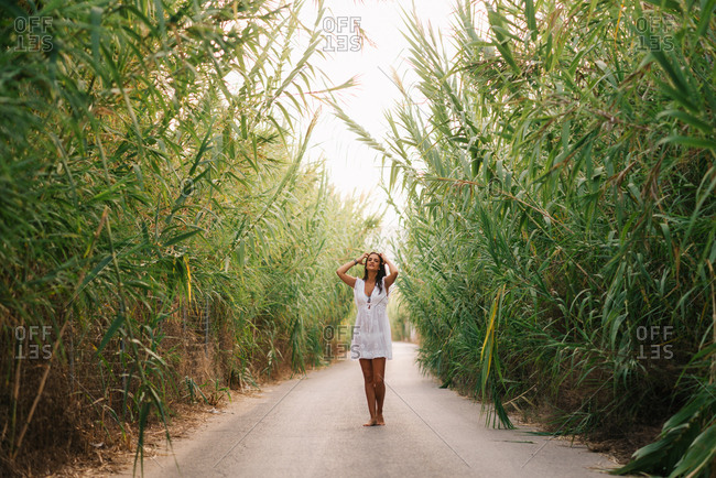 Pretty woman in light white dress straightens hair while walking on avenue among green trees