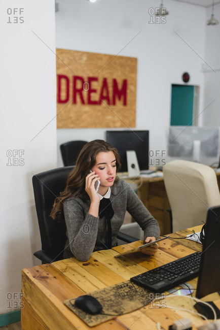 Young woman with the tablet pc talking phone in office. Vertical indoors shot.