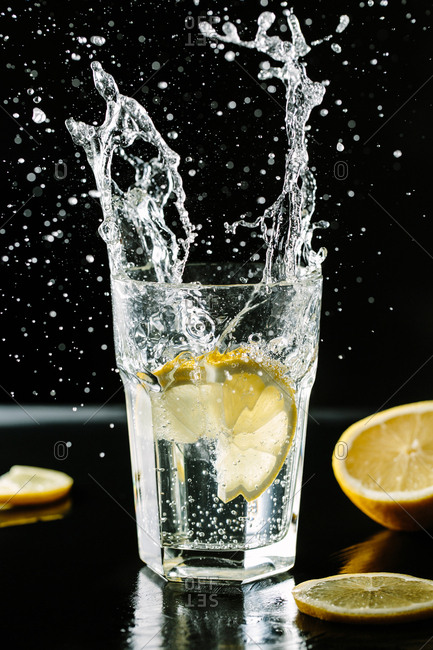 Vertical studio shot of splashes of mineral water with lemon.