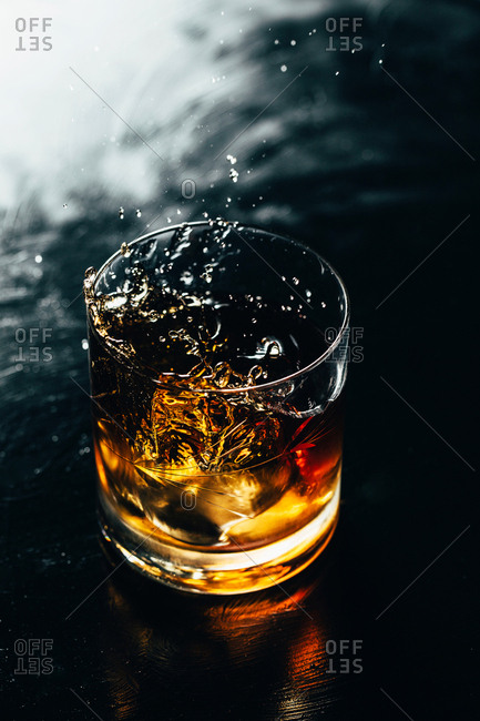 Splashing from glass whiskey on wooden table and tongs.