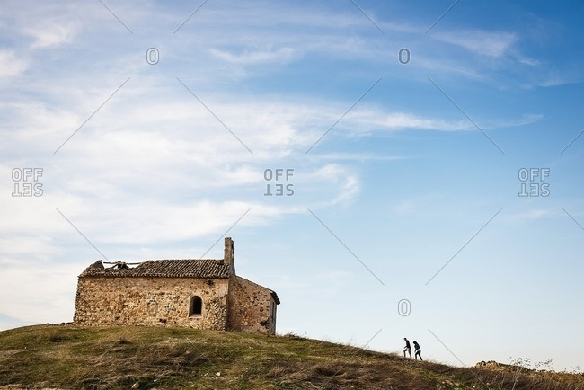 Horizontal outdoors shot of couple walking to rustic old house on a hill