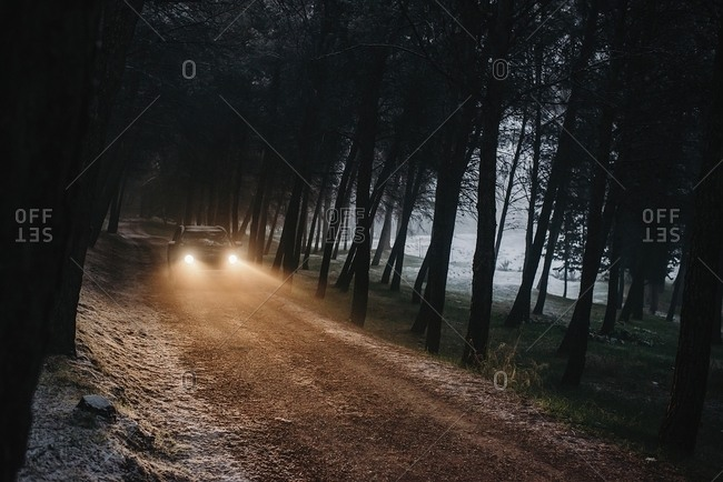 Horizontal outdoors shot of car being driven through the dark forest
