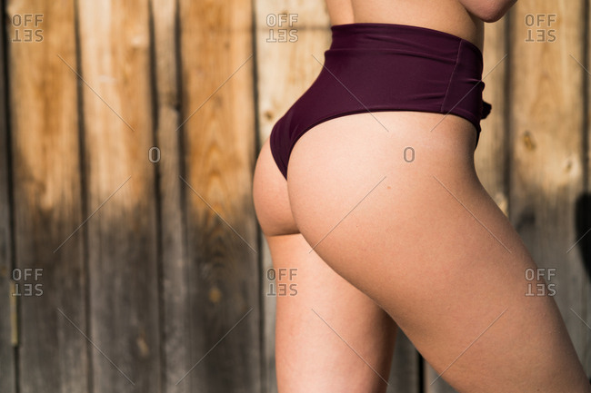 Faceless shot of female bottom in panties posing on background of wooden fence.