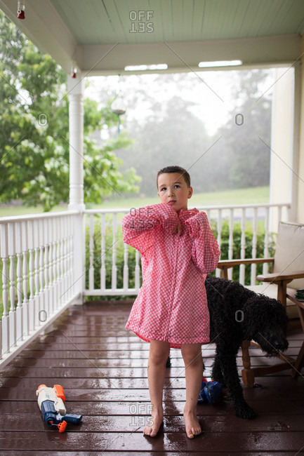 Boy in rain coat on a porch