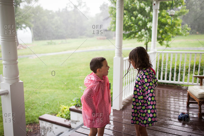 Wet kids on porch in rain coats