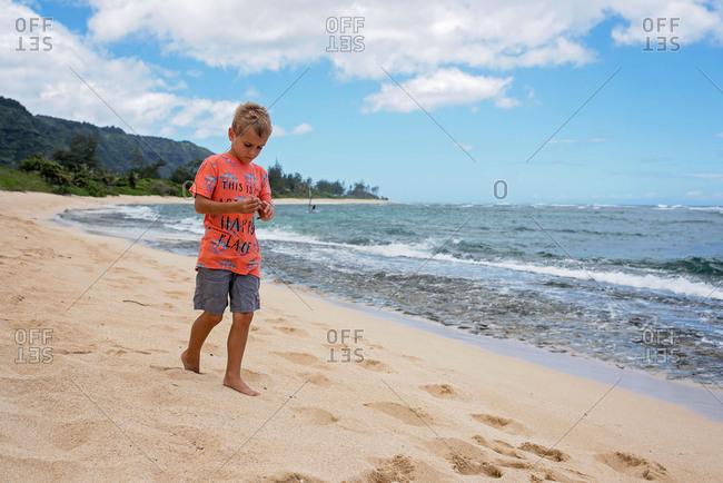 Pensive boy strolling on beach