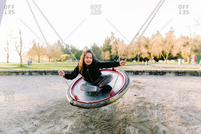 Young girl riding on a saucer swing