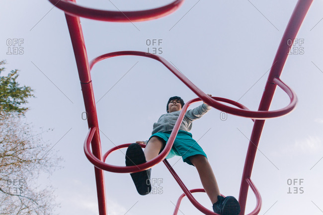 Boy climbing on bars on a playground