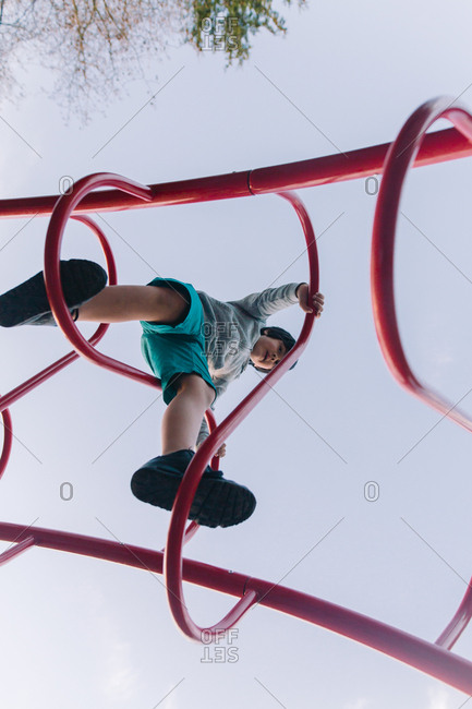 Young boy climbing on bars in a playground