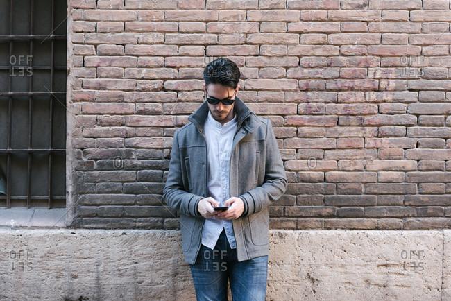 Stylish man using his phone in city