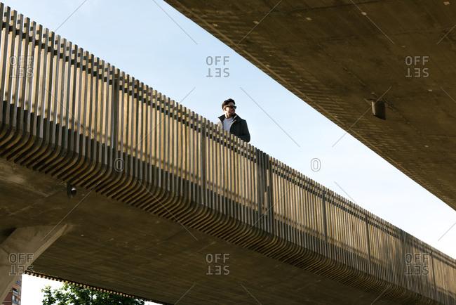 Man crossing footbridge outside building