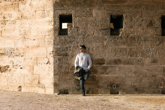 Man leaning against old stone building