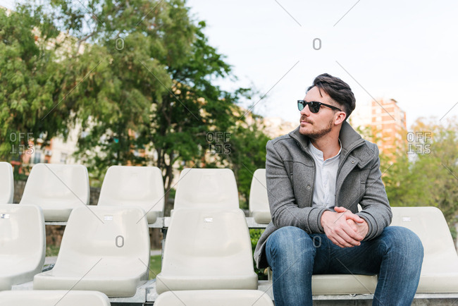 Man on seats in park with sunglasses