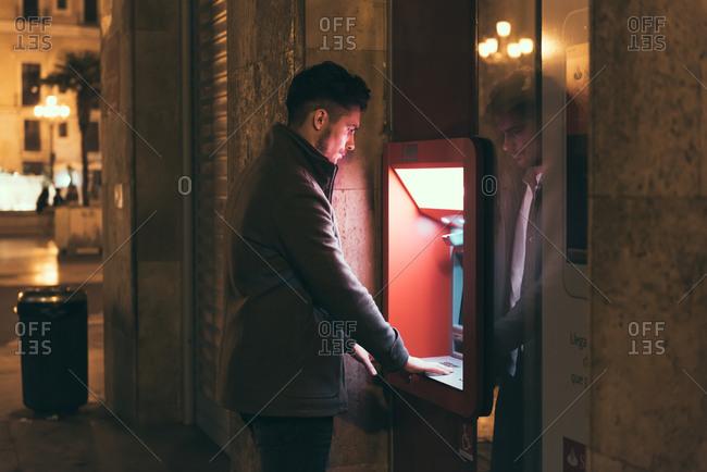 Man at city ATM at night