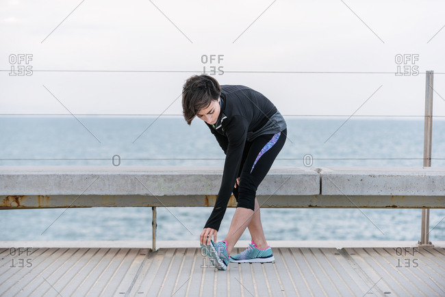 Female runner stretching by sea