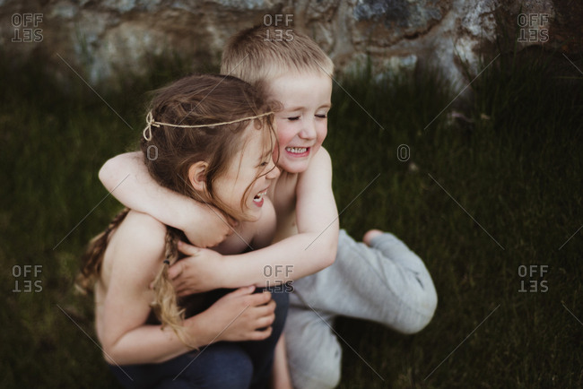 Siblings hugging and laughing together