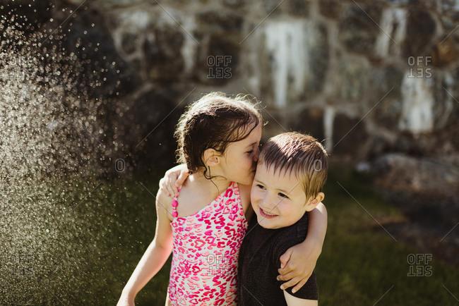 Girl kissing her brother by sprinkler