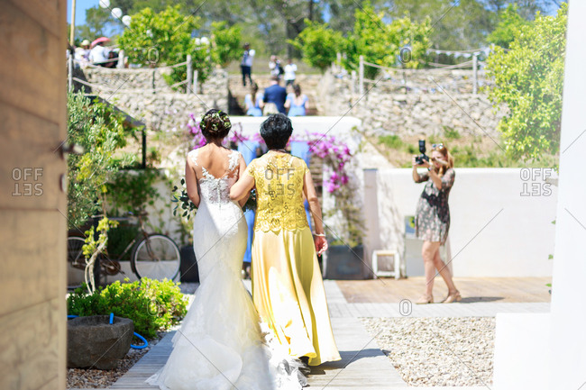 Bride and woman walking outside together