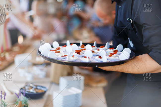 Caterer with tray of food at wedding