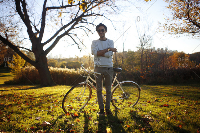 Hip man in fall field with bike