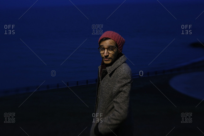Man in coat by shore at night