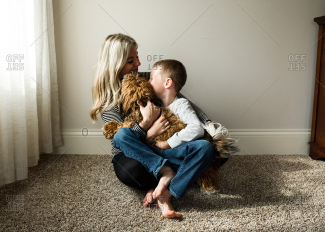 Woman hugging a boy and dog
