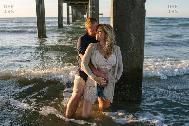 Man holding pregnant woman under dock