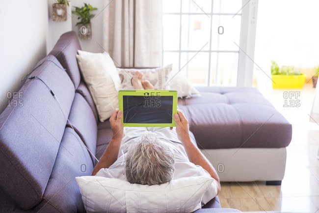 Man lounging on his couch with tablet