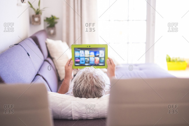 Man lounging on his couch using a tablet