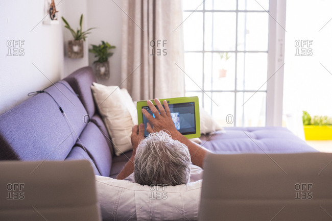 Man lounging on his couch using tablet